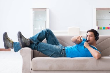 Young handsome man singing karaoke at home