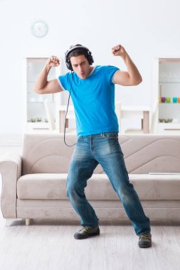 Young handsome man listening to the music and having fun at home