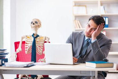 Businessman working with skeleton in office stock vector