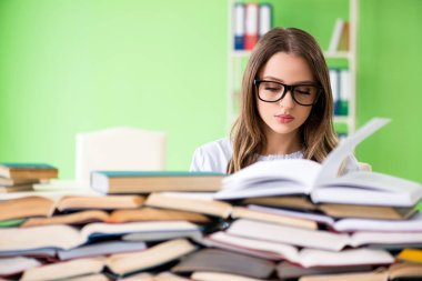 Young female student preparing for exams with many books