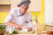 Fotografie Young professional cook preparing salad at kitchen