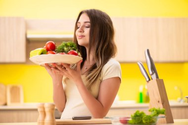 Young woman preparing salad at home in kitchen