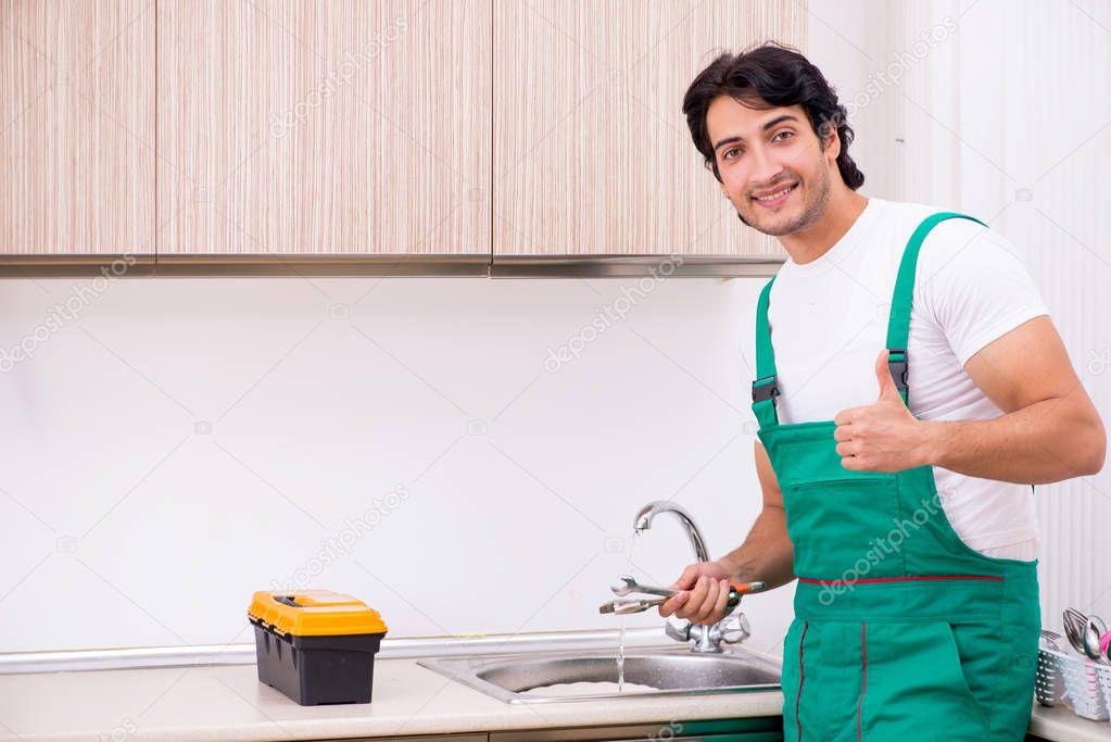 Young plumber repairing tap at kitchen