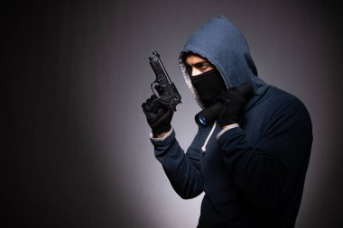 Young gangster in hood on grey background