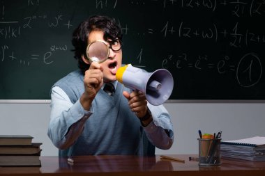 Young math teacher in front of chalkboard