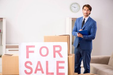 Young handsome realtor selling flat
