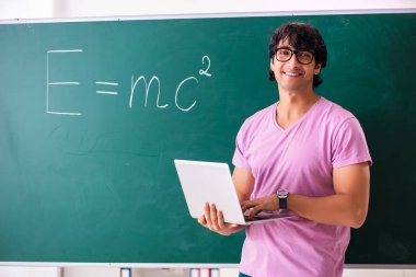 Young male physic standing in front of the green board