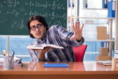 Young funny math teacher in front of chalkboard