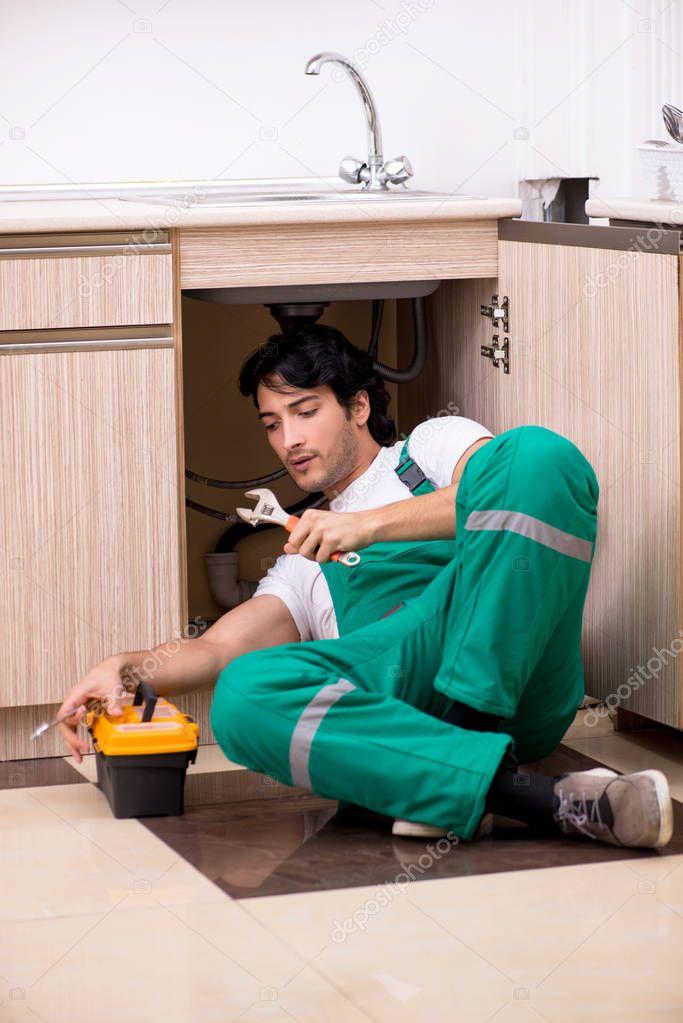 Young plumber repairing wash basin at kitchen