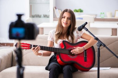 Female beautiful blogger playing guitar