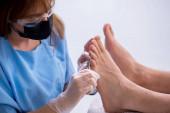 Podologe behandelt Füße während des Eingriffs