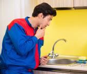 Fotografie Installateur repariert Wasserhahn in Küche