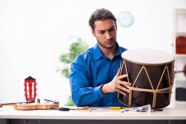 Young male repairman repairing drum
