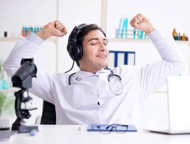 Happy excited doctor listening to music during lunch break in ho