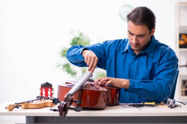 Young male repairman repairing cello