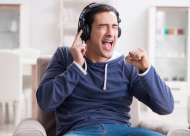 Young man listening to music at home