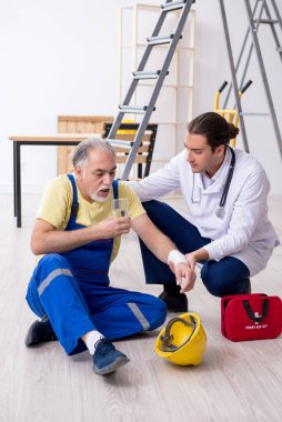 Young male doctor and old contractor in first aid concept