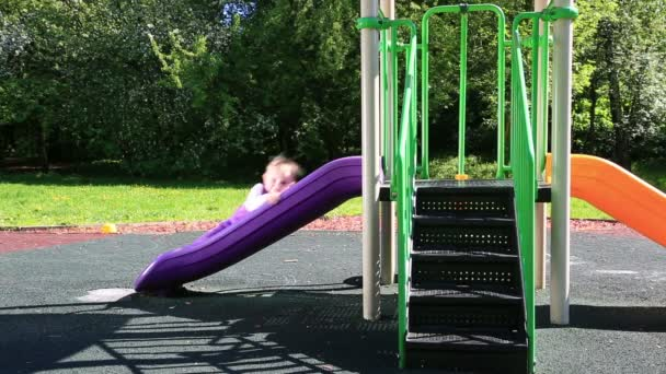 Cute little girl spending time in playground slide