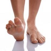 Ritagliate la vista dei piedi femminili stanchi con pelle rosa scortese