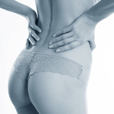 Black and white view of woman in panties touching small of back feeling pain