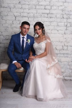 Bride with groom sitting on sofa at studio