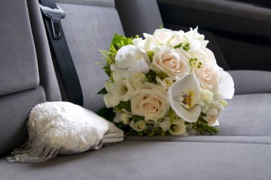 Tender wedding bouquet with white purse on car sit