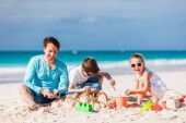 Fotografie Father and kids playing with sand on beach while enjoying summer vacation
