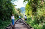 Fotografie Family of father and two kids walking along train tracks in Sri Lanka