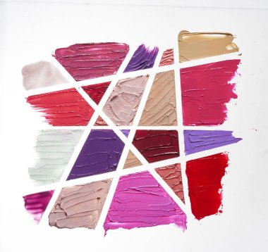 Smears of different colors are made with various cosmetic products isolated on a white background.