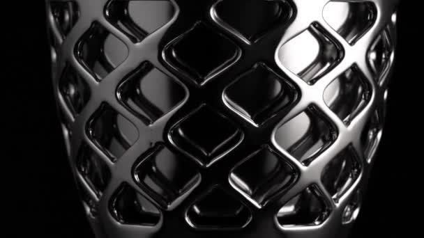 Hladké kruhové pohyby chromované plochy, černé pozadí, abstrakce