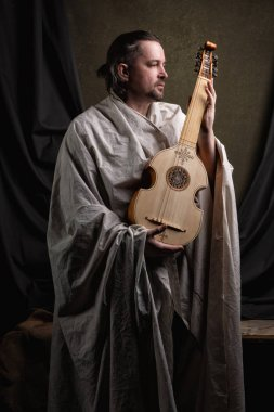 Adult man in historical suit playing viol