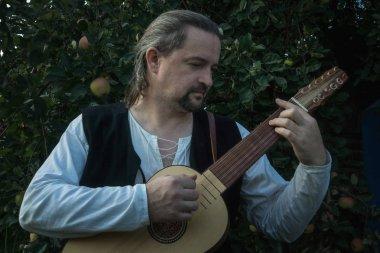 Adult man in historical suit playing vihuela in summer garden