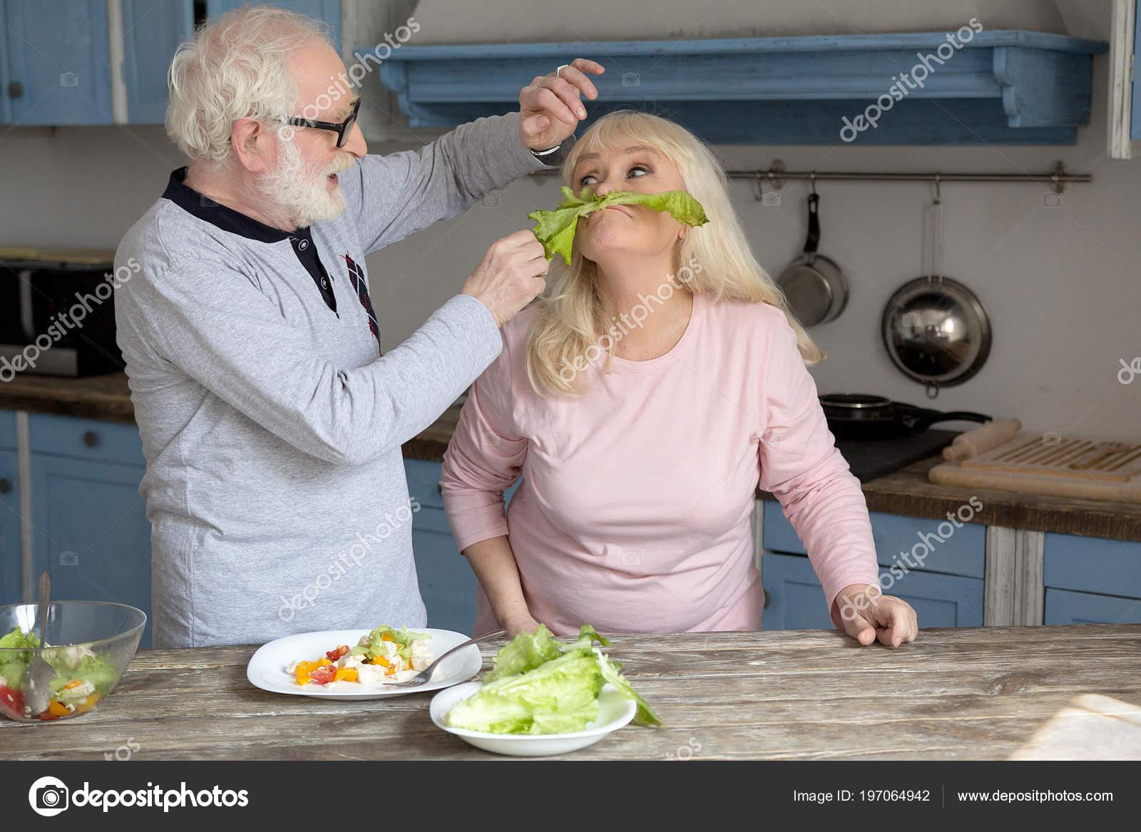 Elderly Couple Having Fun In Kitchen Stock Photo