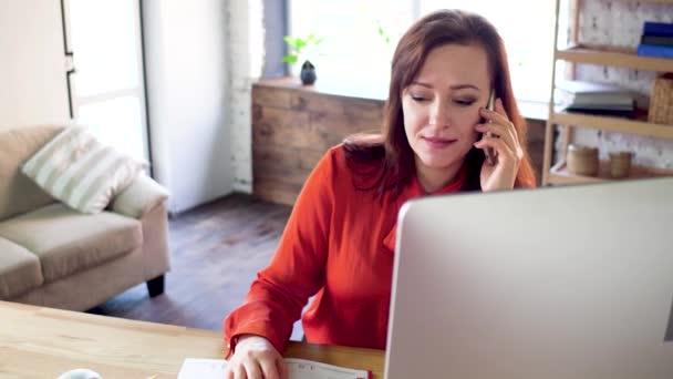 Businesswoman talking on phone in office.