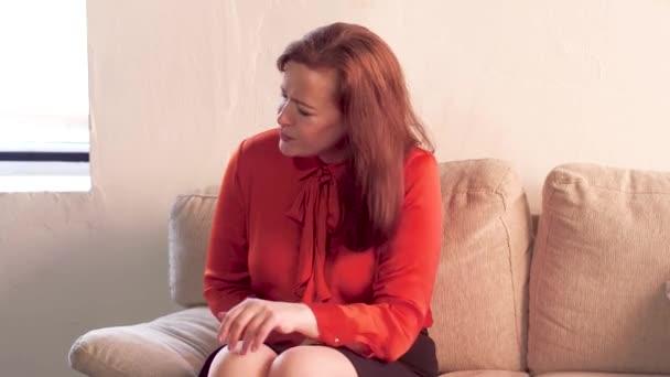 Žena s bolest žaludku na gauči