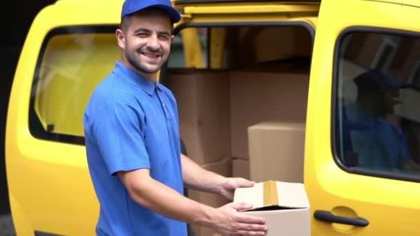 Doručovatel v modré uniformě drží krabice poblíž žlutého auta
