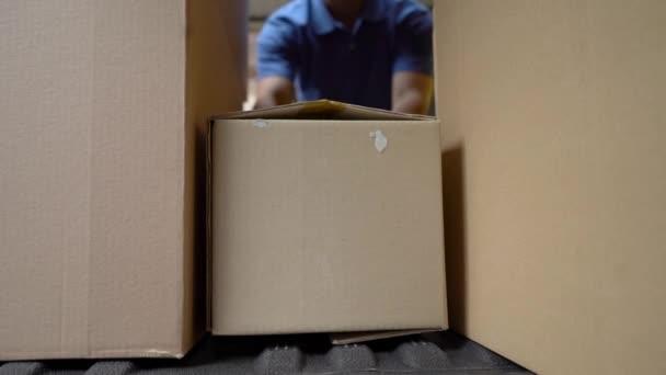 Courier v modré uniformě načte boxy do auta. Záběr z uvnitř auta
