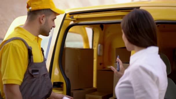 Podnikatelka kontroluje dodávky od kurýra v přírodě poblíž jeho auto žluté uniformě