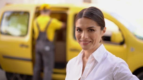Usměvavá podnikatelka ukazuje palcem. Rozmazané dodávka a kurýr na pozadí