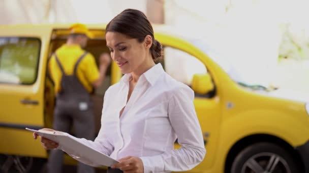 Usmívající se dívka čte dodací doklady na schránky. Courier poblíž žluté auto