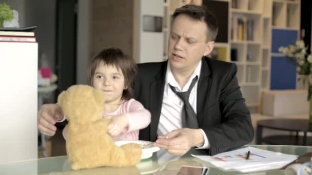 Father in suit working with papers and feeding daughter