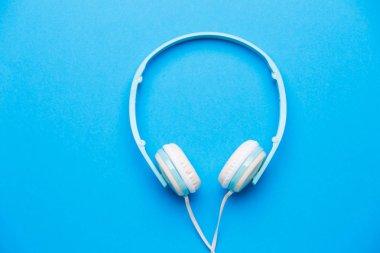 Photo of white headphones on blue background
