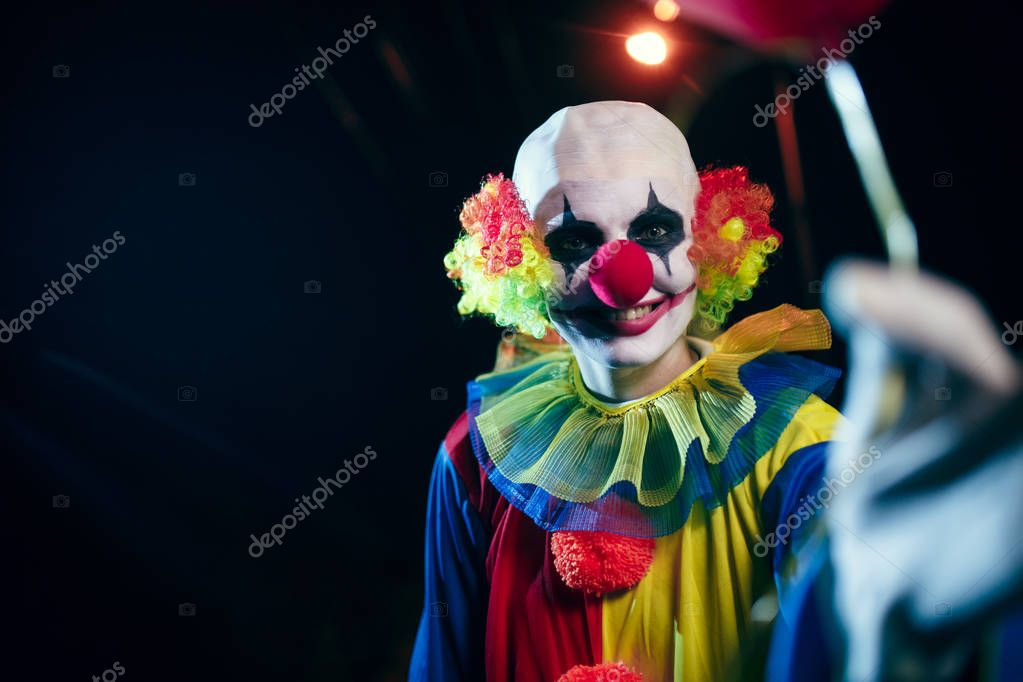 Image of clown with red balloon at night on street