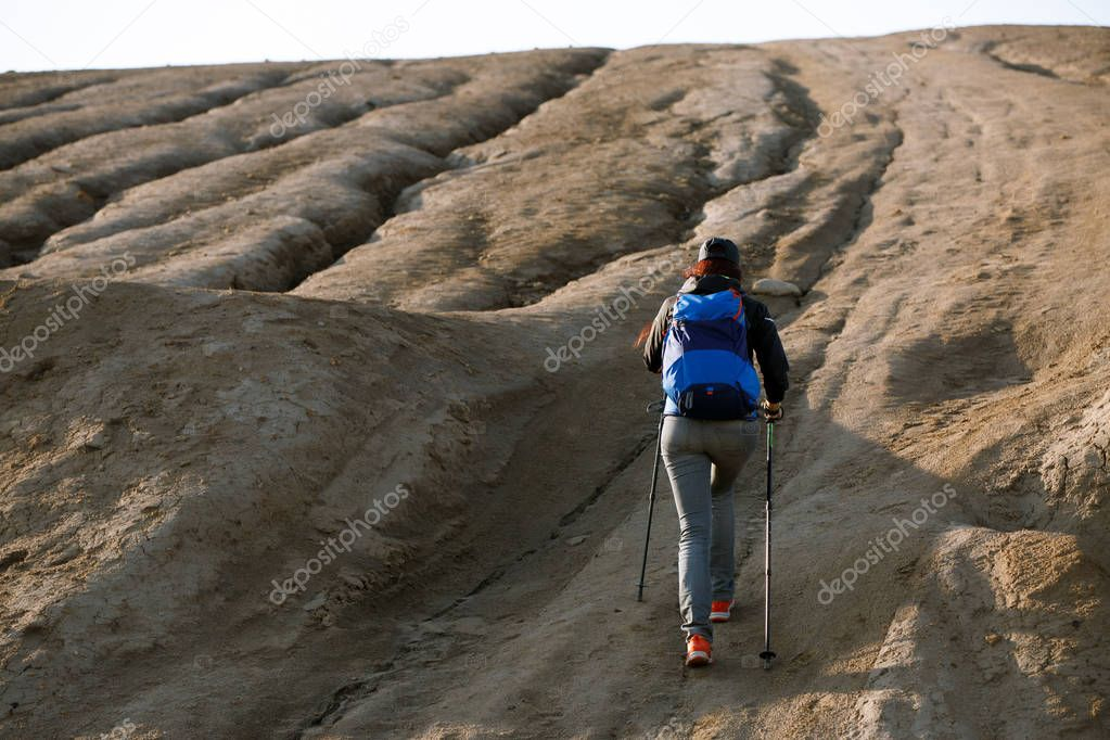 Photo from back of growth of female tourist with backpack and sticks for walking on mountain