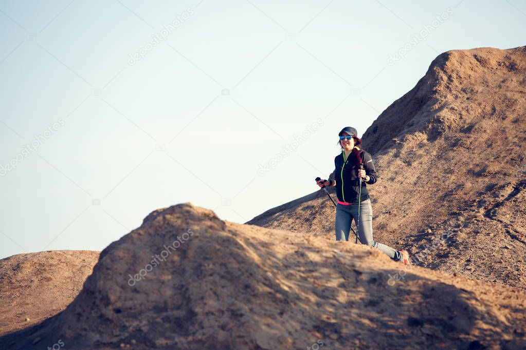 Image in full growth of tourist girl with backpack and sticks for walking on mountain