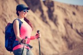 Photo Image of beautiful tourist woman with backpack and walking sticks
