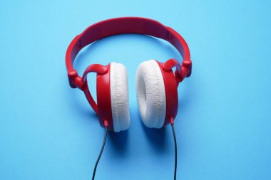 Photo of red with white headphones on empty blue background