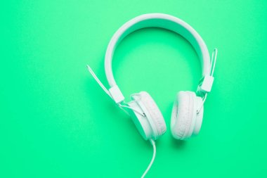 White headphones with cord on an empty green background.