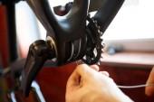 Photo of man repairing bicycle gear