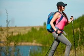 Oldalnézetből young fotó sport lány sétapálca, háttérben a tó és a zöld növényzet